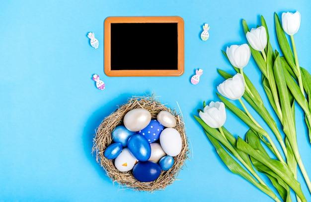 Пасхальные яйца синих цветов в гнезде из соломы, меловой доски, декоративных прищепок и букета белых тюльпанов на синем фоне