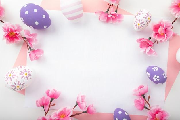 ピンクの背景にイースターエッグ。ハッピーイースターカードの春の花。フラットレイ、上面図。