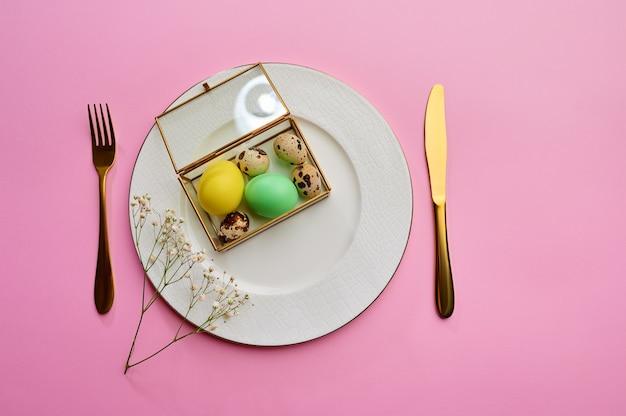 접시와 식기 분홍색 테이블에 부활절 달걀. 봄 나무 꽃과 유월절 음식, 휴일 축하를위한 신선한 꽃 장식, 이벤트 기호