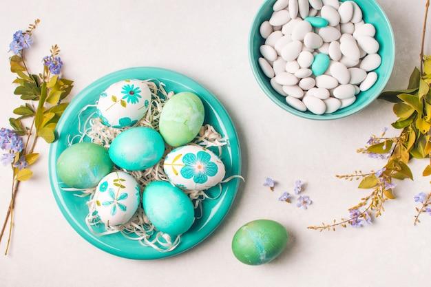 Пасхальные яйца на тарелке возле маленьких камней в миске и цветочных ветках
