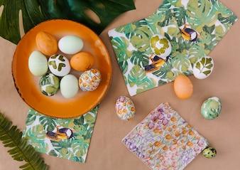 熱帯の塗料と葉を持つナプキンの近くの皿にイースターエッグ