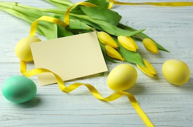 空白のカードと木製のテーブルの上のイースターエッグ