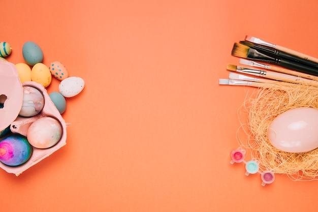 Easter eggs; paint brushes; egg nest on the corner of the orange background