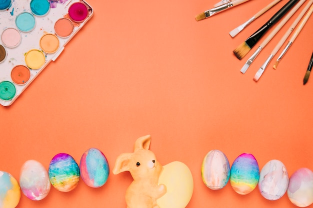 Easter eggs; paint brushes; paint box and rabbit statue on an orange background