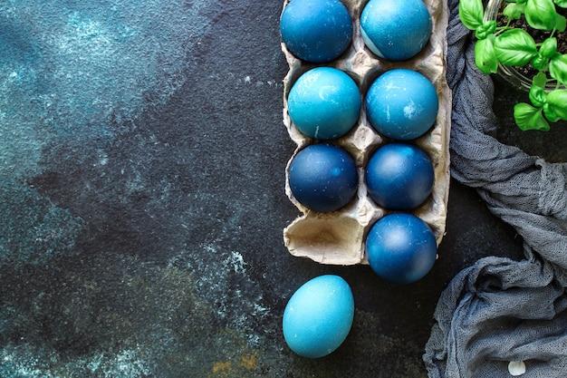 Пасхальные яйца выкрашены в синий цвет, пасхальное угощение праздничный стол деревенская еда