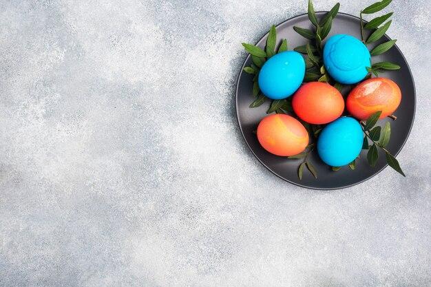 Раскрашенные вручную пасхальные яйца на бетонном столе