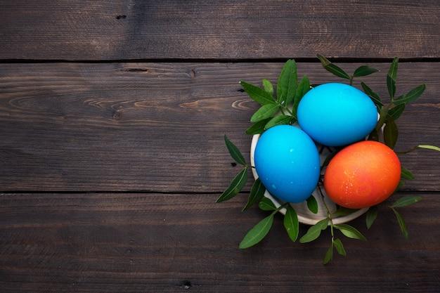 Пасхальные яйца раскрашены вручную на темном деревянном столе, вид сверху, копия пространства. Premium Фотографии