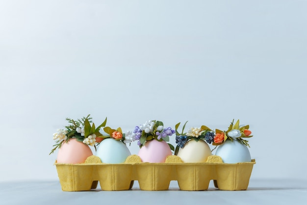 花輪が付いた卵トレイにパステルカラーで描かれたイースターエッグ