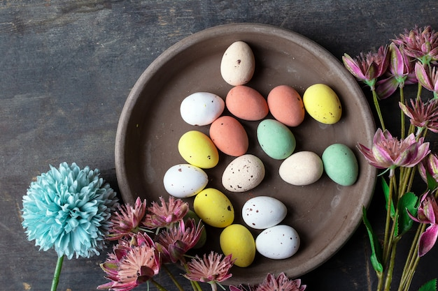 Пасхальные яйца окрашены в пастельных тонах на старинных деревянных фоновой текстуры, бетонные плиты вид окружен различными весенними цветами в современных цветах. вид сверху в стиле ретро