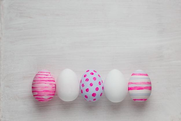 부활절 달걀 흰색 나무 바탕에 파스텔 색상으로 그린.