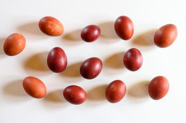 イースターエッグは白い背景にタマネギの殻を描いた。皮をむいた玉ねぎを使った古い自然環境にやさしい方法に従って卵を着色する