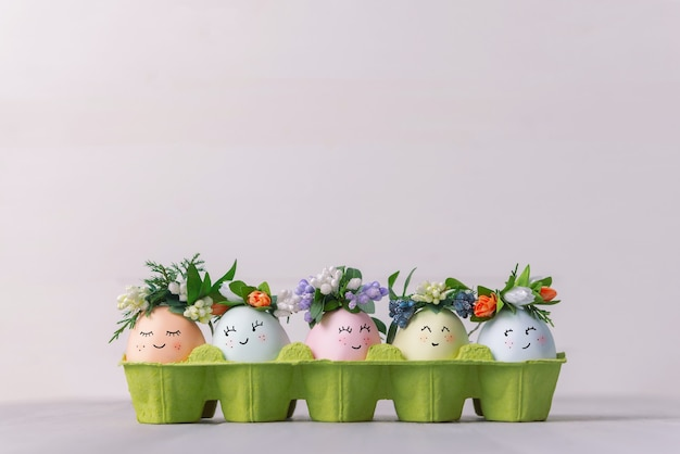 Easter eggs painted in pastel colors in an egg tray with wreaths on them