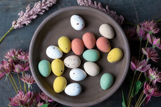 Easter eggs painted in pastel colors on a vintage wooden background texture, concrete look plate surrounded with various spring flowers in modern colors. retro design top view