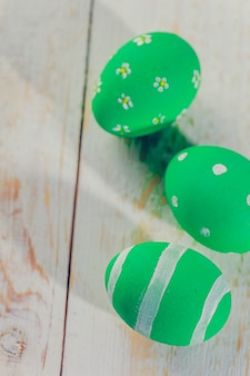 Easter eggs painted in pastel colors on white wooden .