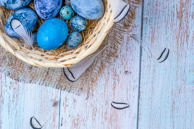 Раскрашенные натуральным красителем пасхальные яйца в деревенском стиле natural яйца в гнезде из сена в плетеной корзине на мешковине