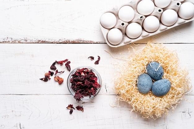 Пасхальные яйца, расписанные натуральными красками, цветы гибискуса, чай каркаде, на белом старом деревянном столе, красные весенние цветы тюльпаны.