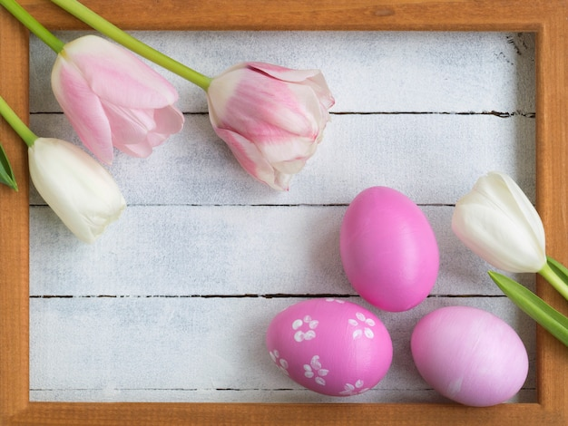 Easter eggs, photo frame, tulips on a white wooden background.