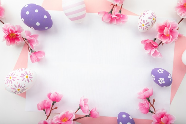 Easter eggs on pink background. spring flowers for happy easter card. flat lay, top view.