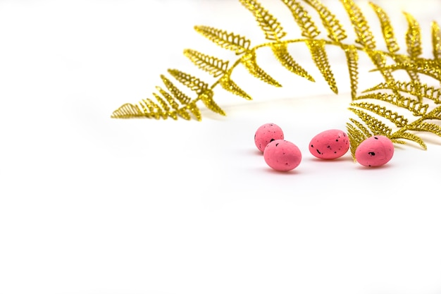 Easter eggs pink color and gold fern branches