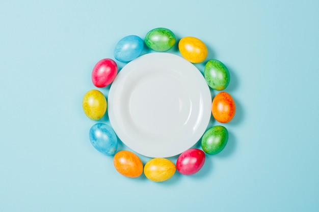 Easter eggs on a plate on a blue background. concept of celebrating easter. flat lay, top view
