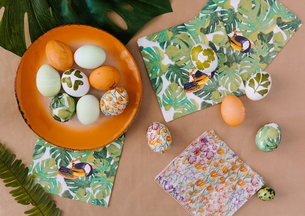 Easter eggs on plate near napkins with tropical paints and leaves