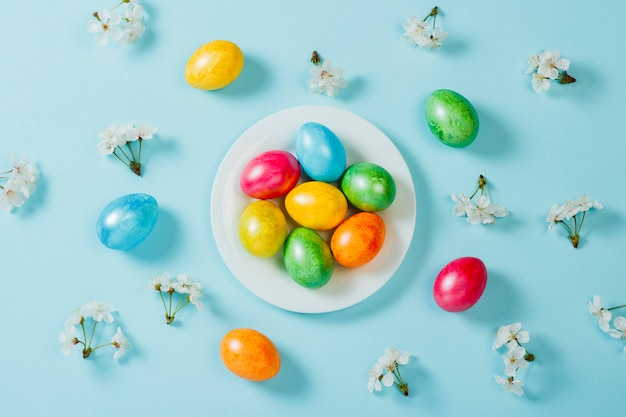Easter eggs on a plate and spring flowers on a blue background background. concept of celebrating easter. flat lay, top view