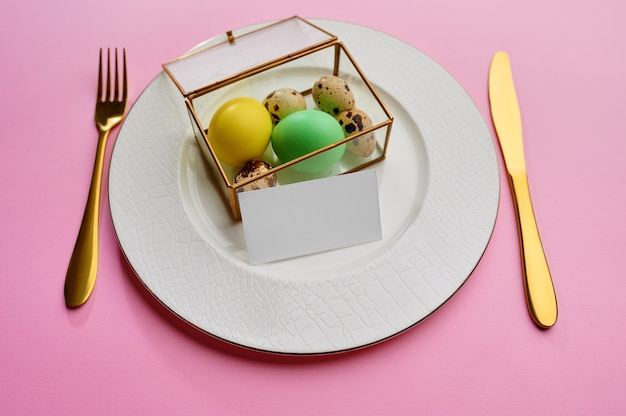 Easter eggs on plate and tableware on pink background
