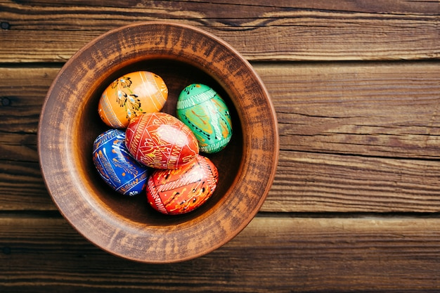 Easter eggs on a plate on a wooden background