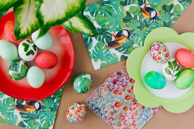 Easter eggs on plates near napkins with tropical paints