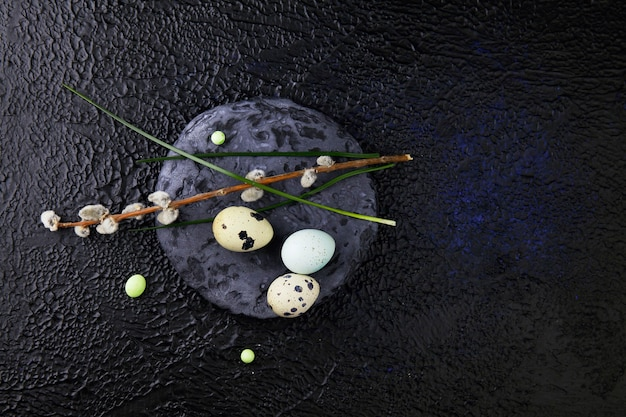 Easter eggs and pussy willow branches standing on a round slate stone