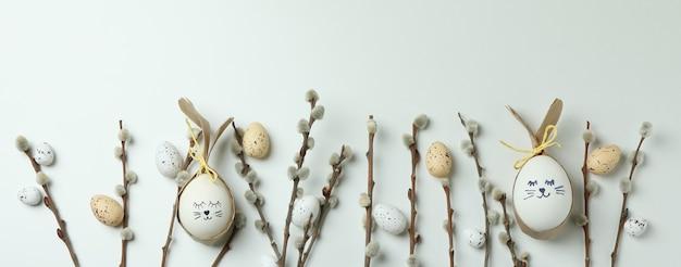 Пасхальные яйца, перепелиные яйца и сережки на белом фоне