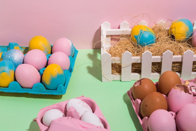 Easter eggs in racks and on hay on table