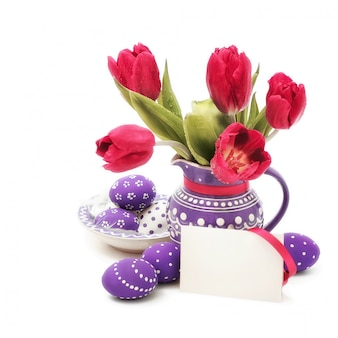 Easter eggs and red tulips in purple vase on white, text space