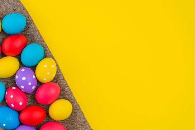 Пасхальные яйца разбросаны по холсту на столе