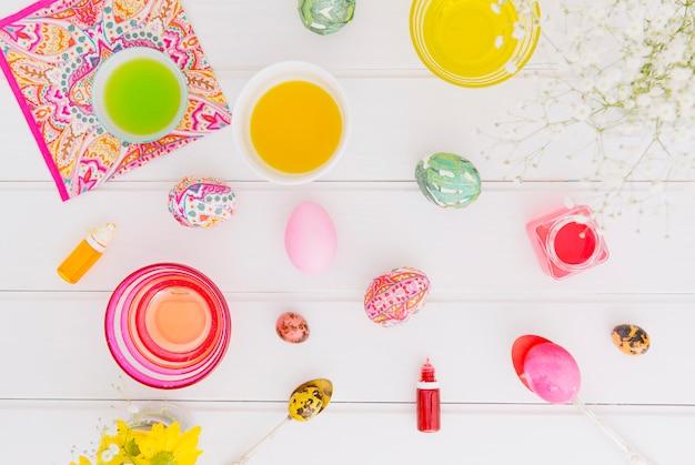 Uova di pasqua tra cucchiai vicino tovagliolo, fiore ramoscello e tazze con liquido di tintura