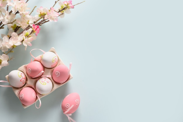 Easter eggs and spring blooming flowers on blue