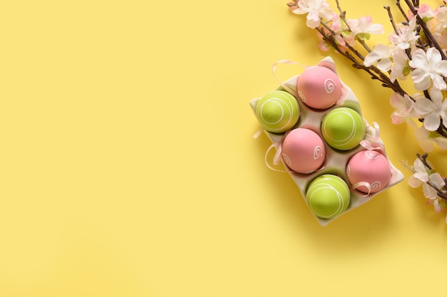 Easter eggs and spring blooming flowers on yellow