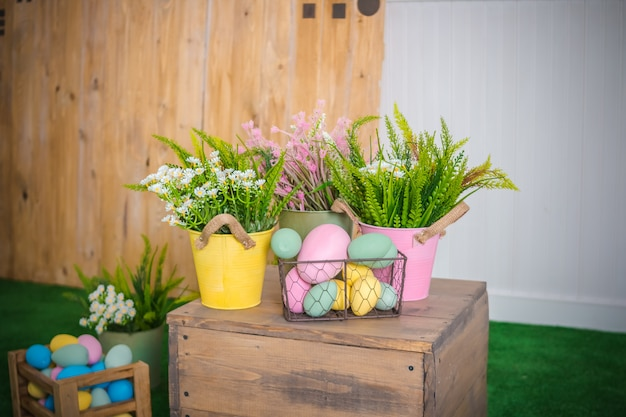 Easter eggs and spring flowers in basket, box on wooden table