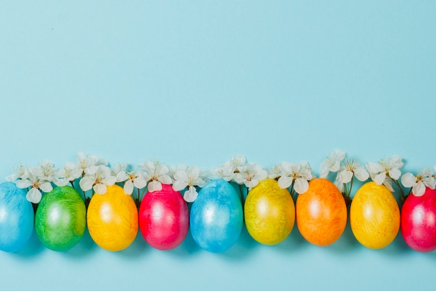 Easter eggs and spring flowers on a blue background. concept of celebrating easter. flat lay, top view