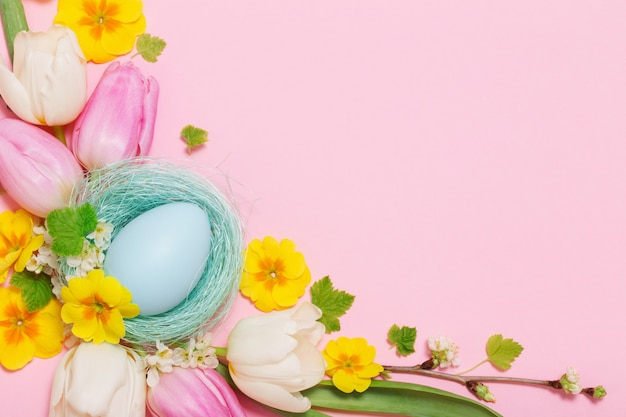 Easter eggs and spring flowers on pink background