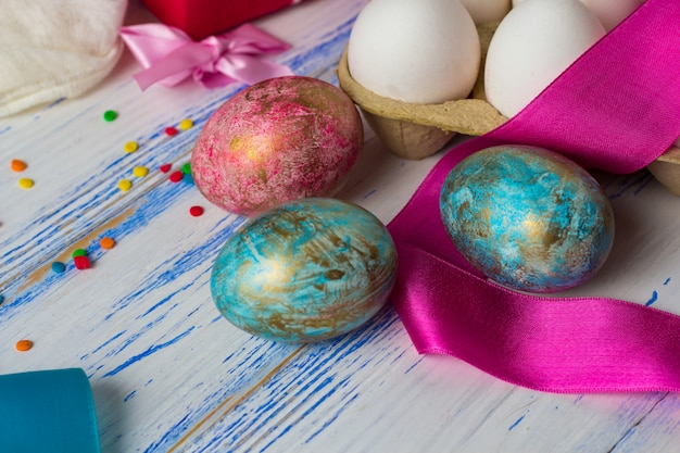 Easter eggs, sweets, ribbons on the white wooden table