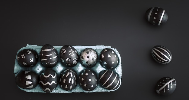 Easter eggs in tray on black isolated table