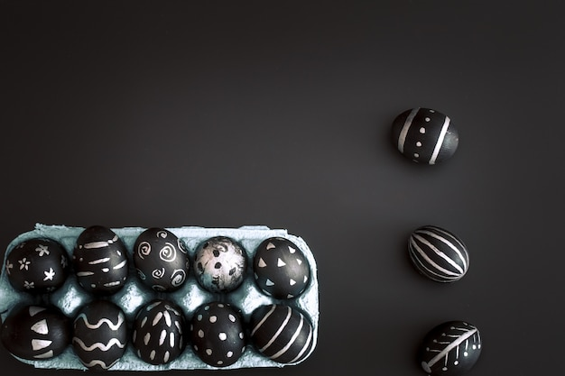 Easter eggs in tray on black isolated wall