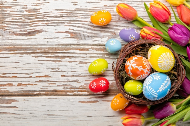 Easter eggs and tulips on wooden planks