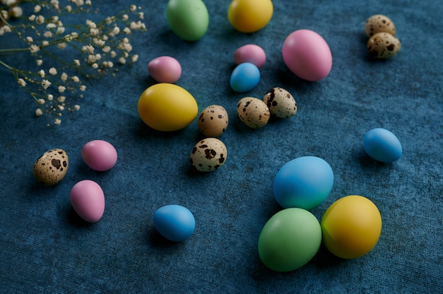 Easter eggs and wildflowers on blue cloth background
