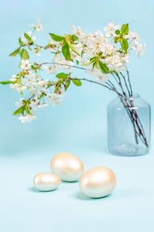 青い背景の花瓶に開花桜の枝の花束とイースターエッグ。季節性のコンセプト、春、はがき、休日。フラットレイ、コピースペース、テキスト用のスペース。閉じる。
