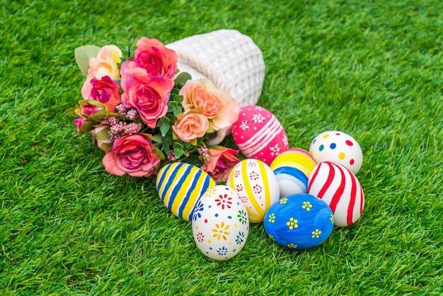 Пасхальные яйца с искусственным цветком на свежей зеленой траве