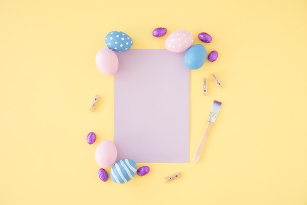 Easter eggs with blank purple paper on table