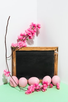 Easter eggs with chalkboard and flowers branch on table