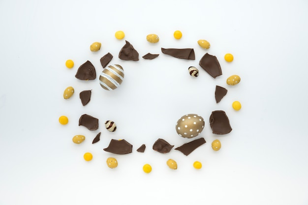 Easter eggs with chocolate pieces on table